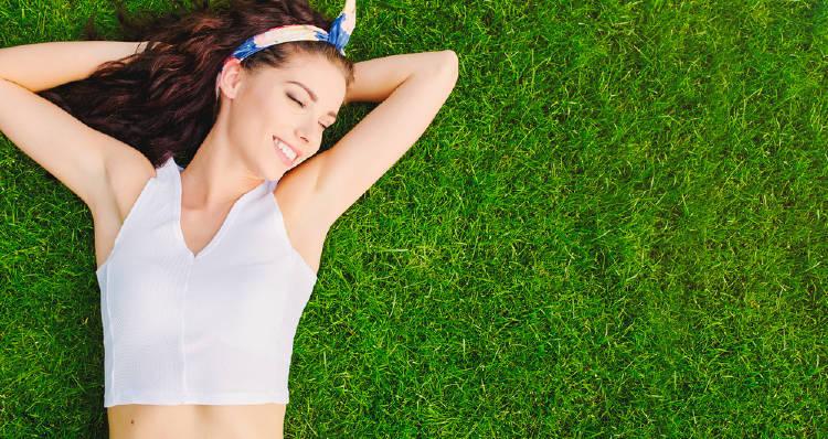 Mujer recostada sobre el pasto