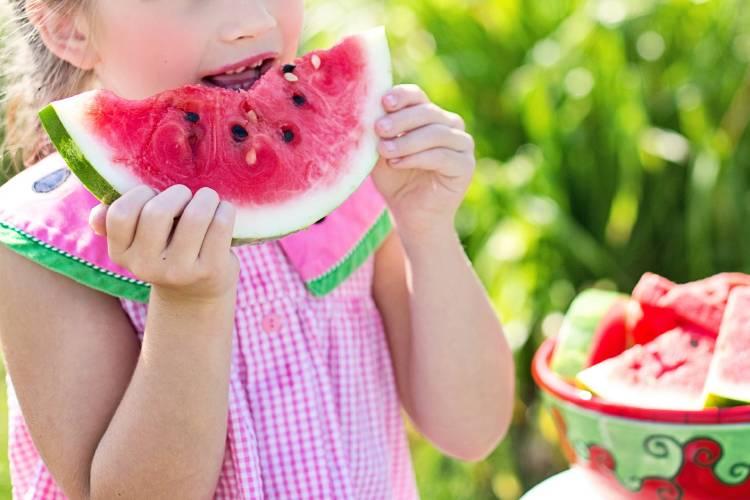 Una niña comiendo sandía