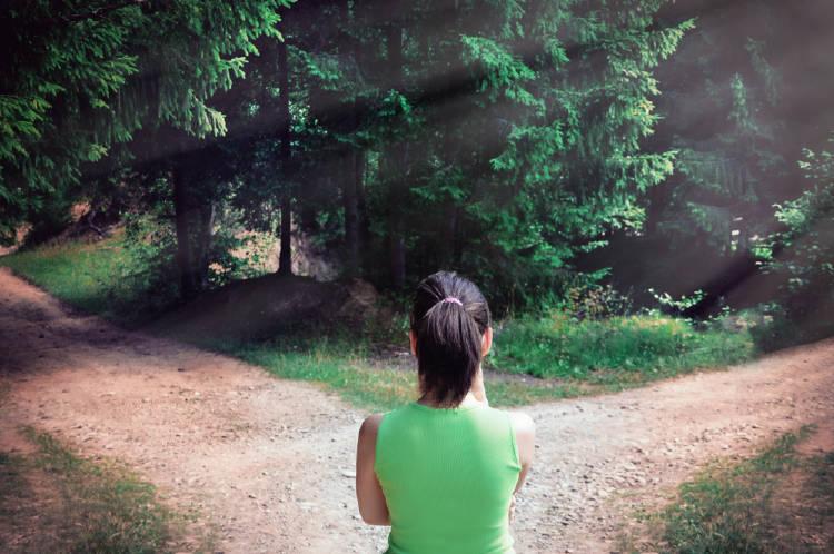 una mujer observa dos caminos para tomar la decision correcta