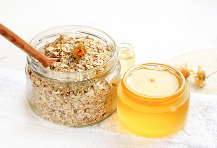 Recipiente transparente con hojuelas de avena y una cuchara de madera al lado de un recipiente transparente con miel de abejas
