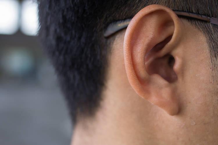 La oreja de un hombre que usa gafas