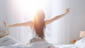mujer al amanecer se despereza en su cama